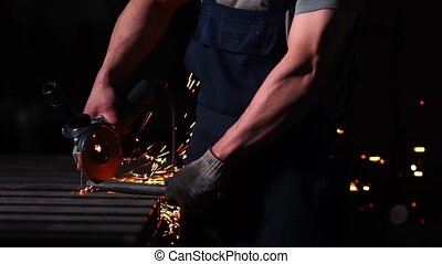 closeup on electric saw and hands of worker with sparks. man...