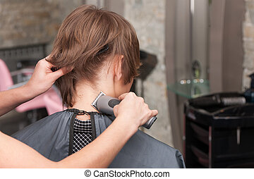 Closeup on female hairdresser cutting hair of man client using trimmer. back view of man sitting in chair in hair salon