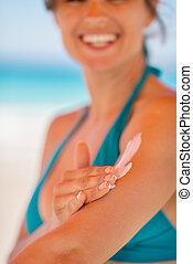 Closeup on female hand applying sun block creme on arm