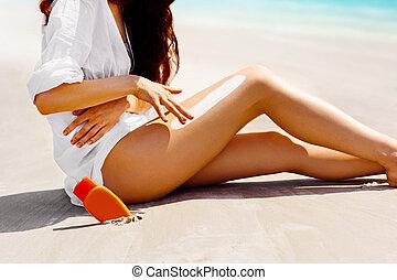 Closeup on female hand applying sun screen creme on legs