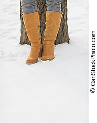 Closeup on female legs in winter boots on snow