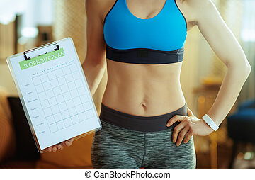 Closeup on fit sports woman in modern house showing meal plan