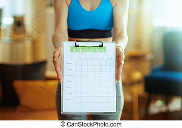 Closeup on fit woman at modern home showing meal plan