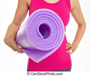 Closeup on fitness mat in hand of fitness woman
