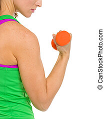 Closeup on fitness woman making exercise with dumbbells