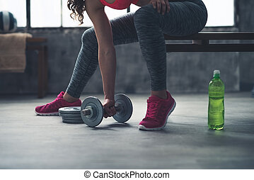 Closeup on fitness woman taking dumbbell from the floor in...