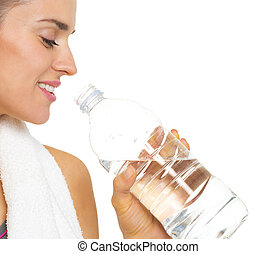 Closeup on fitness young woman drinking water