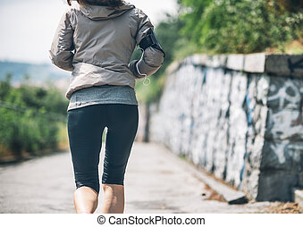 Closeup on fitness young woman jogging in the city park. rear view