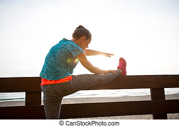 Closeup on fitness young woman stretching on beach in the evening