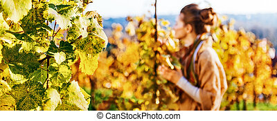 Closeup on grape branch and young woman in autumn vineyard in background