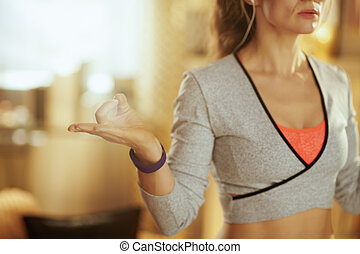 Closeup on hands of active woman doing yoga at modern home