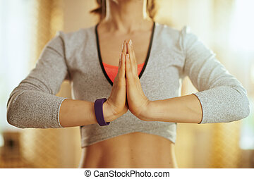 Closeup on hands of fit woman doing yoga at modern home