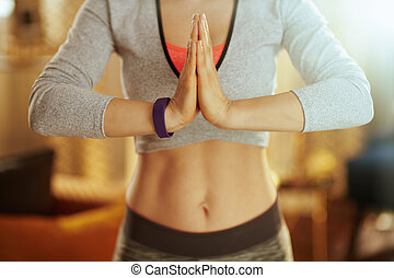 Closeup on hands of fitness woman doing yoga at modern home