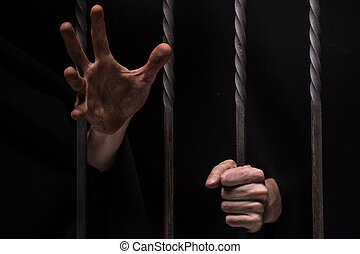closeup on hands of man sitting in jail. Man behind jail...
