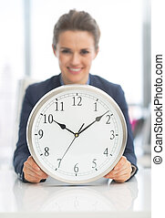 Closeup on happy business woman with clock