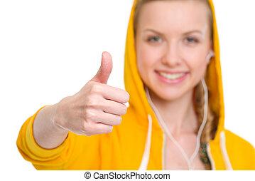 Closeup on happy teenager girl in earphones showing thumbs up