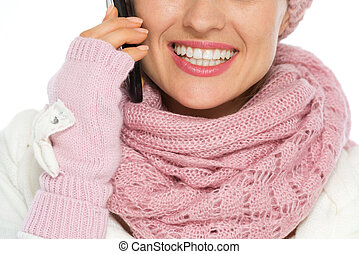 Closeup on happy woman in winter clothing speaking mobile