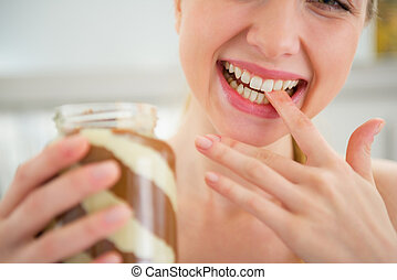 Closeup on happy young woman licking chocolate butter from finge