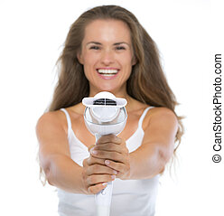 Closeup on happy young woman pointing hairdryer in camera