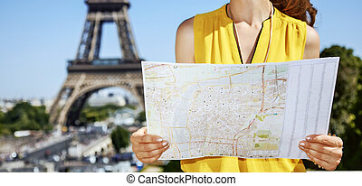 Closeup on happy young woman with map in Paris, France