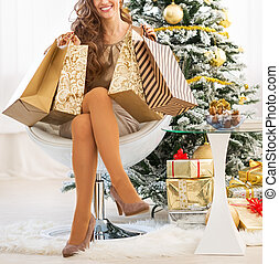 Closeup on happy young woman with shopping bags near christmas tree