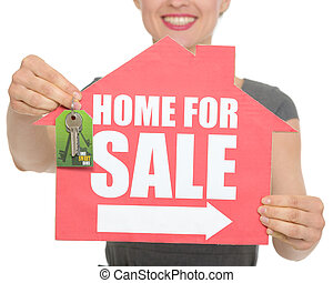 Closeup on home for sale sign and keys holding by happy female. HQ photo. Not oversharpened. Not oversaturated