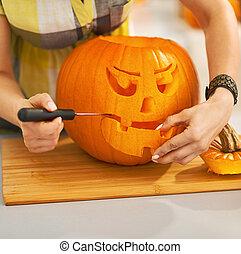 Closeup on housewife carving a big orange pumpkin...