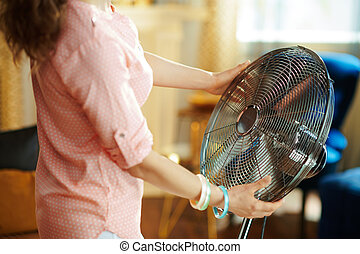 Closeup on housewife cooling down in front of working fan