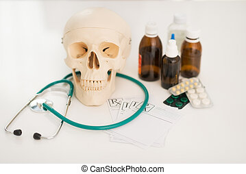 Closeup on human skull stethoscope and drugs on table