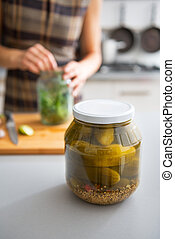 Closeup on jar of marinated cucumbers on table and housewife...