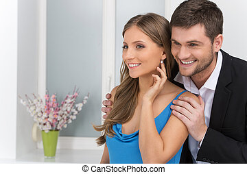 Closeup on man looking at earring on girl's ear. man standing behind woman wearing jewelry