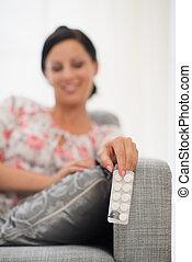 Closeup on medicine in hand of happy woman
