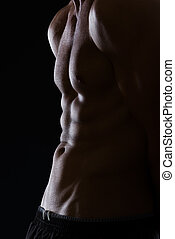 Closeup on muscular male torso with abdominal muscles on ...