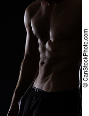 Closeup on muscular male torso with abdominal muscles on...