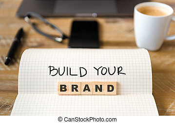 Closeup on notebook over vintage desk background, front focus on wooden blocks with letters making Build Your Brand text