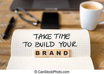 Closeup on notebook over vintage desk background, front focus on wooden blocks with letters making Take Time To Build Your Brand text