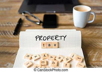 Closeup on notebook over vintage desk background, front focus on wooden blocks with letters making Property Tax text