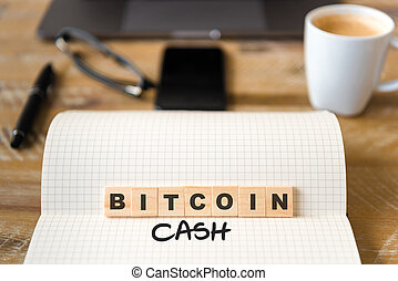 Closeup on notebook over vintage desk background, front focus on wooden blocks with letters making Bitcoin Cash text