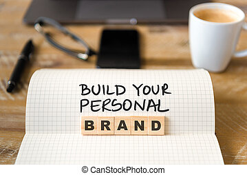 Closeup on notebook over vintage desk background, front focus on wooden blocks with letters making Build Your Personal Brand text