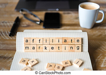 Closeup on notebook over wood table background, focus on wooden blocks with letters making Affiliate Marketing words