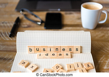 Closeup on notebook over wood table background, focus on wooden blocks with letters making Business Ideas words
