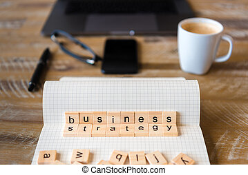 Closeup on notebook over wood table background, focus on wooden blocks with letters making Business Strategy words