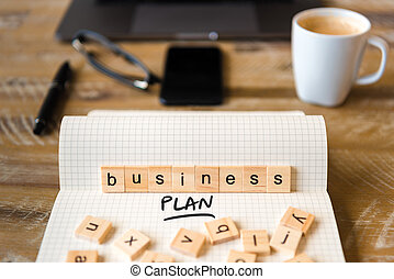 Closeup on notebook over wood table background, focus on wooden blocks with letters making Business Plan text
