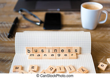 Closeup on notebook over wood table background, focus on wooden blocks with letters making Business Manager words