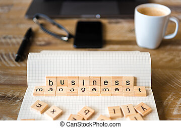 Closeup on notebook over wood table background, focus on wooden blocks with letters making Business Management words
