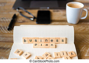 Closeup on notebook over wood table background, focus on wooden blocks with letters making Business Plan words