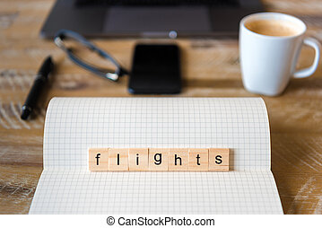 Closeup on notebook over wood table background, focus on wooden blocks with letters making Flights word