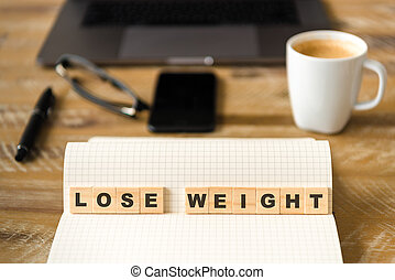 Closeup on notebook over wood table background, focus on wooden blocks with letters making LOSE WEIGHT words