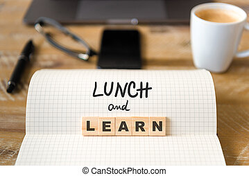 Closeup on notebook over wood table background, focus on wooden blocks with letters making Lunch and Learn text