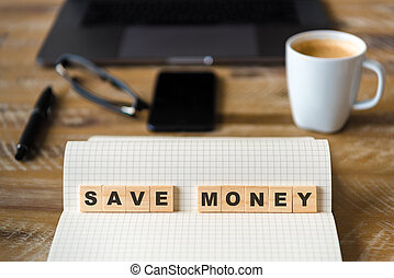 Closeup on notebook over wood table background, focus on wooden blocks with letters making SAVE MONEY words